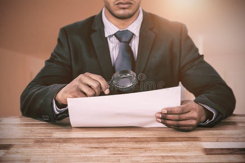 Imagen compuesta del hombre de negocios que mira el documento a través de la lupa imagenes de archivo