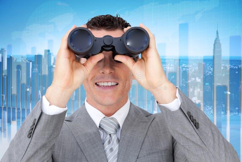 Imagen compuesta del hombre de negocios que sostiene los prismáticos imagen de archivo libre de regalías