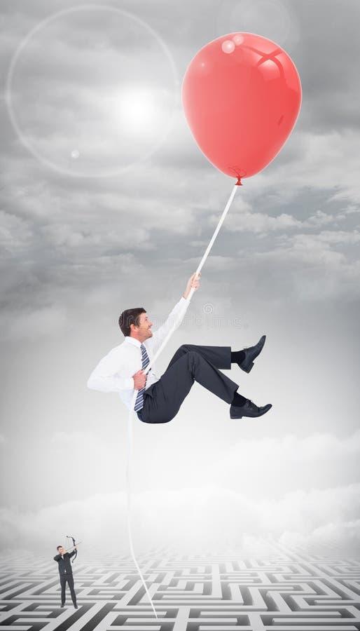 Imagen compuesta del hombre de negocios que tira un arco y una flecha foto de archivo