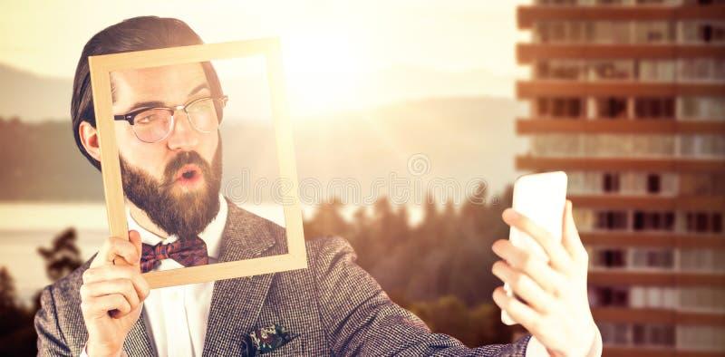 Imagen compuesta del hombre de negocios que toma el selfie mientras que lleva a cabo el marco fotografía de archivo