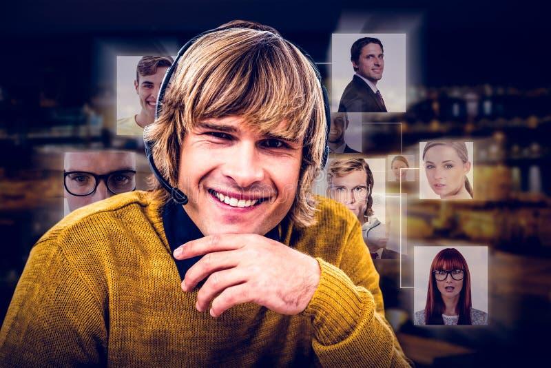 Imagen compuesta del hombre de negocios sonriente del inconformista usando las auriculares fotografía de archivo libre de regalías