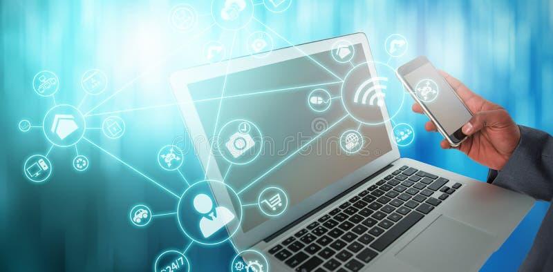 Imagen compuesta del hombre de negocios usando el ordenador portátil y el teléfono móvil imagen de archivo