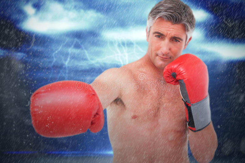 Imagen compuesta del hombre del ajuste que perfora con los guantes de boxeo fotos de archivo