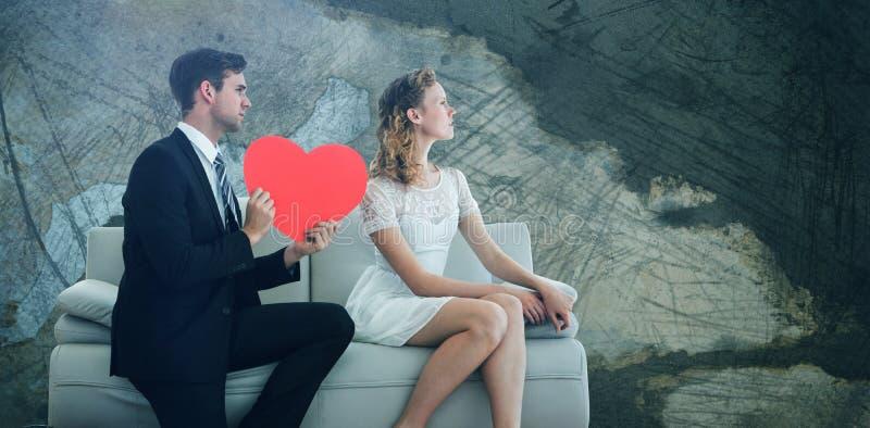 Imagen compuesta del hombre que muestra el papel en forma de corazón rojo a la mujer mientras que se sienta en el sofá imagenes de archivo