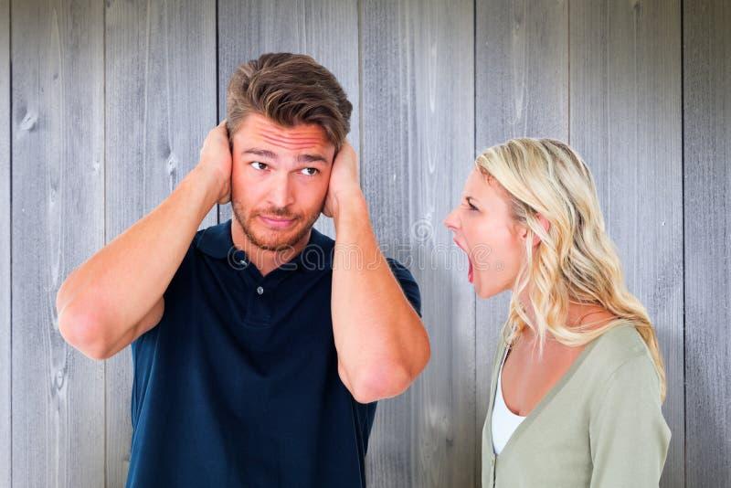 Imagen compuesta del hombre que no escucha su novia de grito foto de archivo libre de regalías