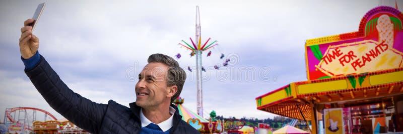 Imagen compuesta del hombre sonriente que toma un seflie foto de archivo