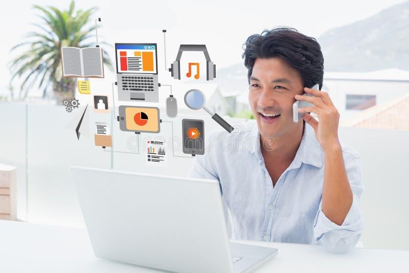 Imagen compuesta del hombre sonriente usando su ordenador portátil y de hablar en el teléfono fotografía de archivo