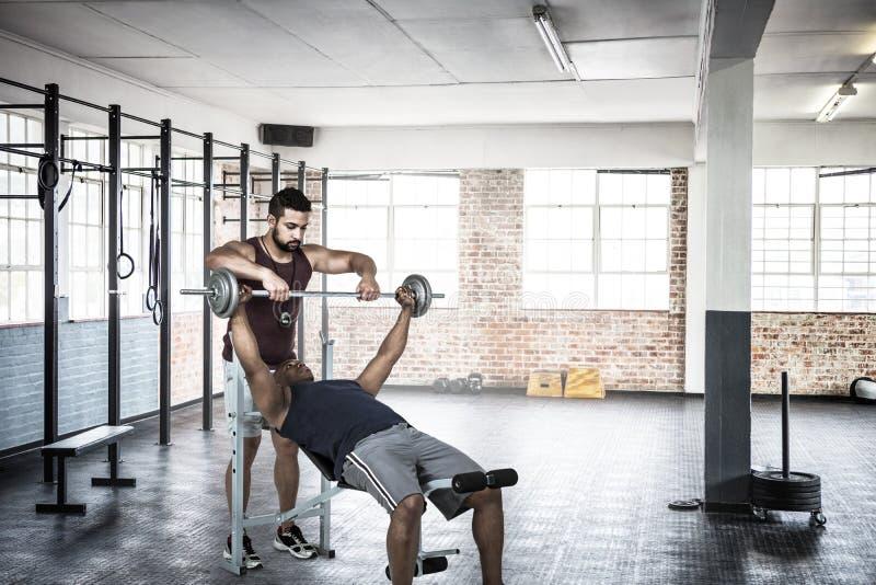 Imagen compuesta del instructor que ayuda al hombre muscular a levantar el barbell imagenes de archivo