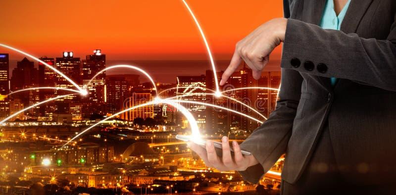 Imagen compuesta del midsection de la empresaria que usa el teléfono móvil imagenes de archivo