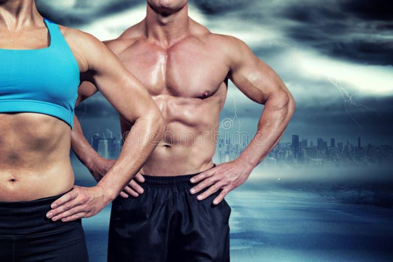 Imagen compuesta del midsection de la mujer muscular y del hombre que se colocan con las manos en cadera imagen de archivo libre de regalías