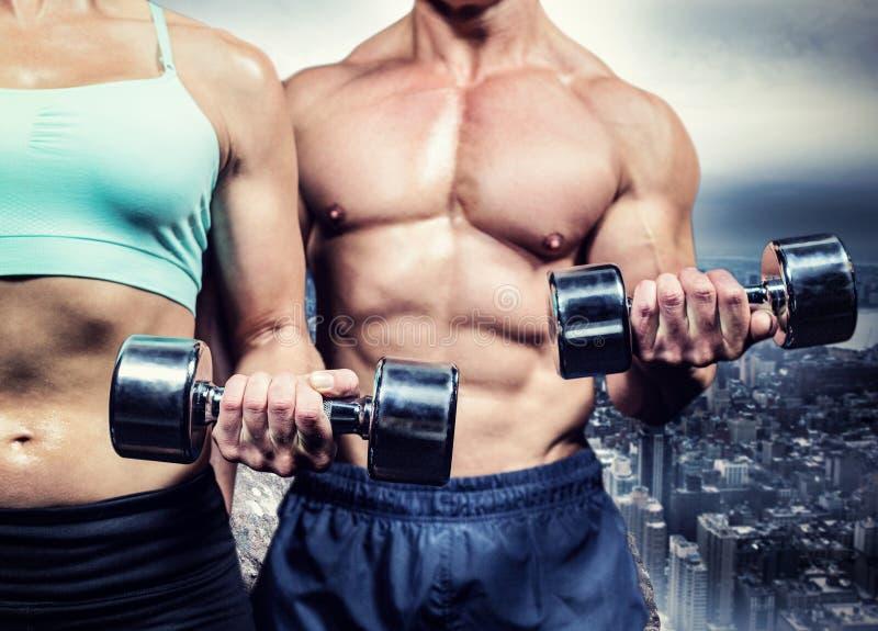 Imagen compuesta del midsection de la mujer y del hombre que ejercitan con pesas de gimnasia fotografía de archivo