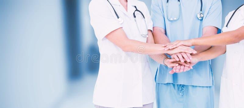 Imagen compuesta del midsection de los doctores que ponen las manos juntas fotos de archivo libres de regalías