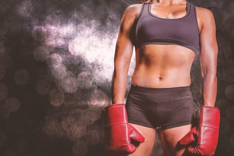 Imagen compuesta del midsection del boxeador de sexo femenino con los guantes fotografía de archivo