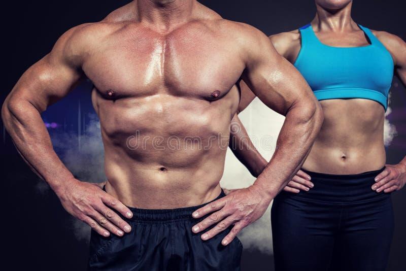 Imagen compuesta del midsection del hombre muscular y de la mujer que se colocan con las manos en cadera foto de archivo libre de regalías
