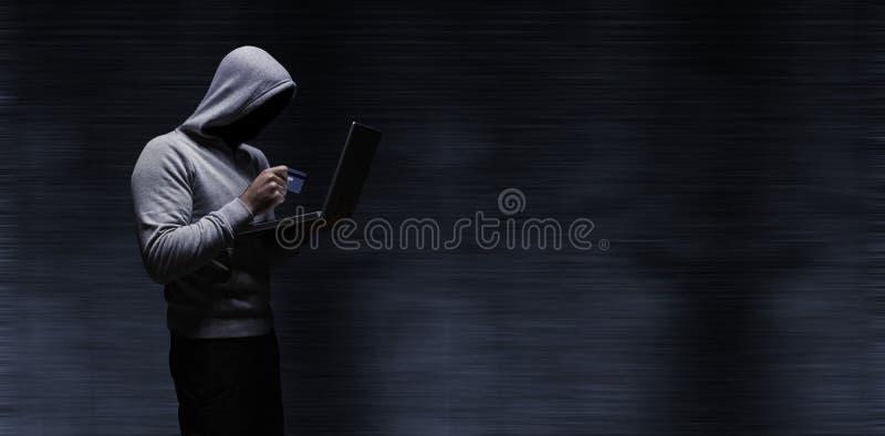 Imagen compuesta del pirata informático que usa el ordenador portátil mientras que sostiene la tarjeta de crédito imagenes de archivo