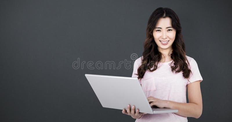 Imagen compuesta del retrato de la mujer feliz que sostiene el ordenador portátil fotografía de archivo libre de regalías