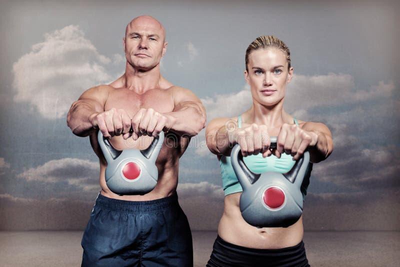Imagen compuesta del retrato de los kettlebells de elevación musculares del hombre y de la mujer foto de archivo