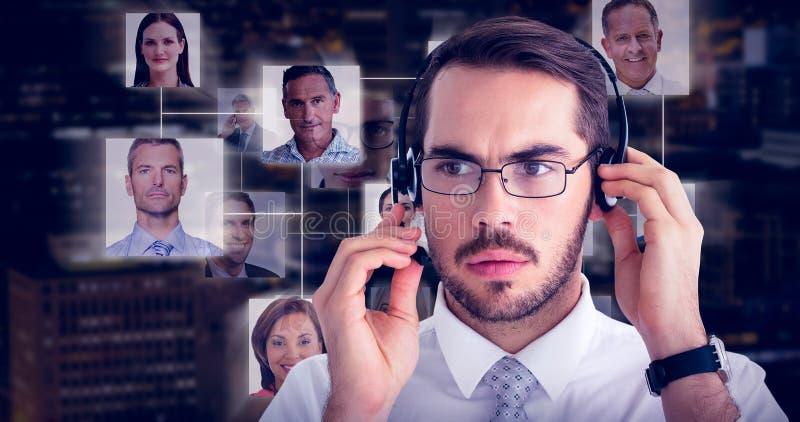 Imagen compuesta del retrato de un hombre de negocios enfocado con el auricular fotos de archivo libres de regalías