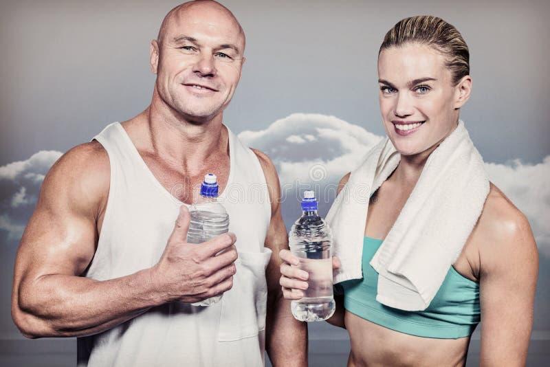 Imagen compuesta del retrato del hombre y de la mujer confiados del atleta con la botella de agua imagenes de archivo