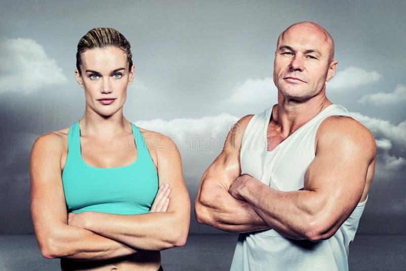 Imagen compuesta del retrato del hombre y de la mujer del atleta con los brazos cruzados fotos de archivo