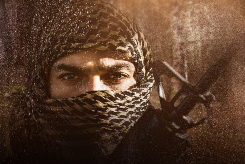 Imagen compuesta del retrato del soldado con la cara cubierta que sostiene el rifle foto de archivo