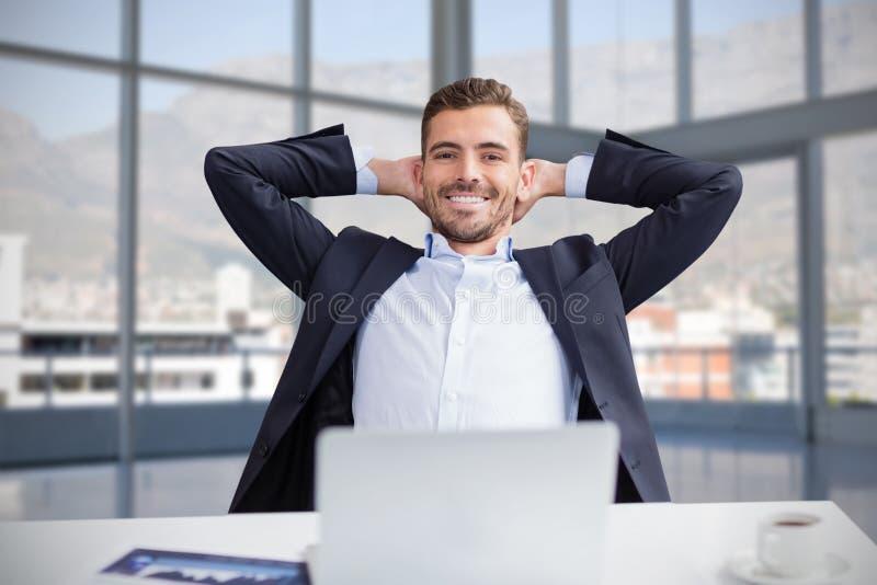 Imagen compuesta del retrato del hombre de negocios sonriente con las manos detrás de la cabeza que se sienta contra la parte pos fotografía de archivo