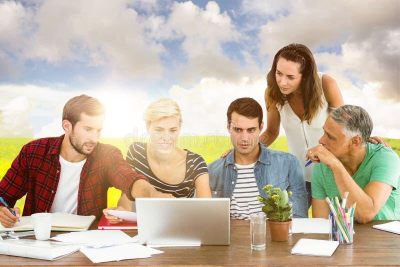 Imagen compuesta del trabajo en equipo usando el ordenador portátil junto imágenes de archivo libres de regalías