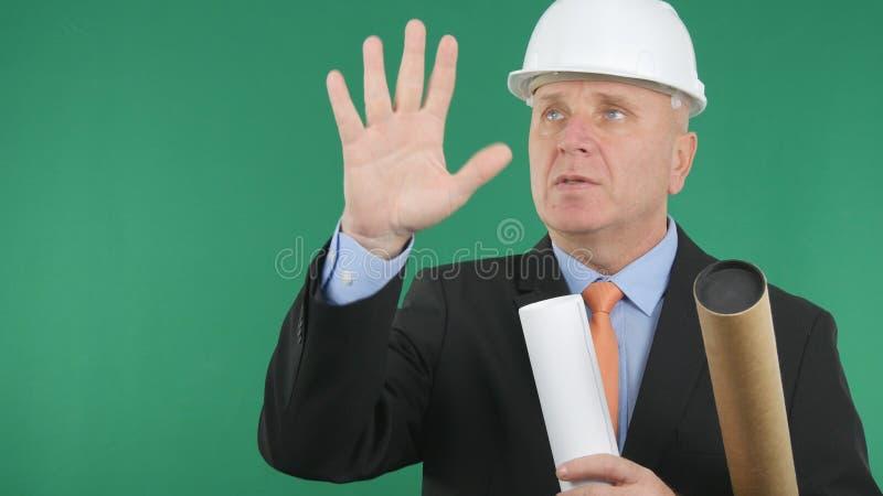 Imagen con ingeniero serio con planes y proyectos haciendo gestos manuales imagen de archivo