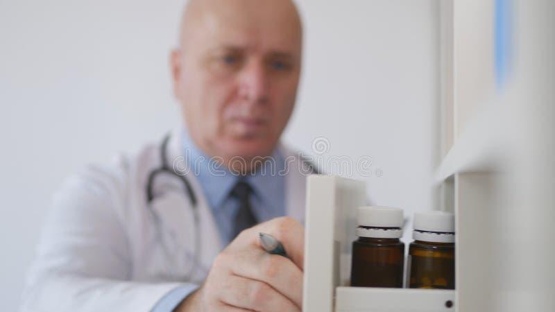 Imagen con un doctor en la oficina del hospital que abre un cajón con las píldoras y las drogas fotos de archivo