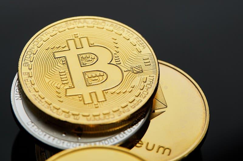 Imagen conceptual de diverso cryptocurrency con los bitcoins en la tabla oscura, primer, foco selectivo imagen de archivo