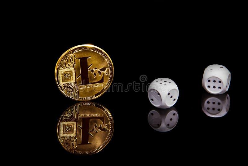 Imagen conceptual de la moneda del litecoin de la moneda del cripto del oro en superficie negra del espejo al lado de dados foto de archivo libre de regalías