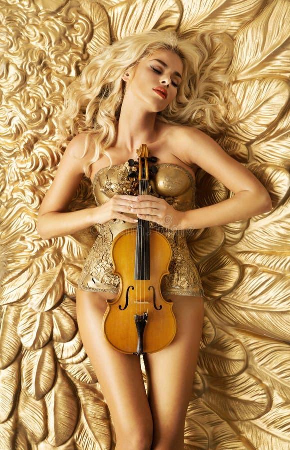 Imagen conceptual de la mujer de oro que sostiene un violín fotografía de archivo