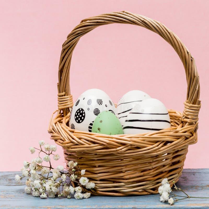 Imagen conceptual de Pascua con los huevos de Pascua pintados en una cesta delante del fondo rosado fotos de archivo libres de regalías