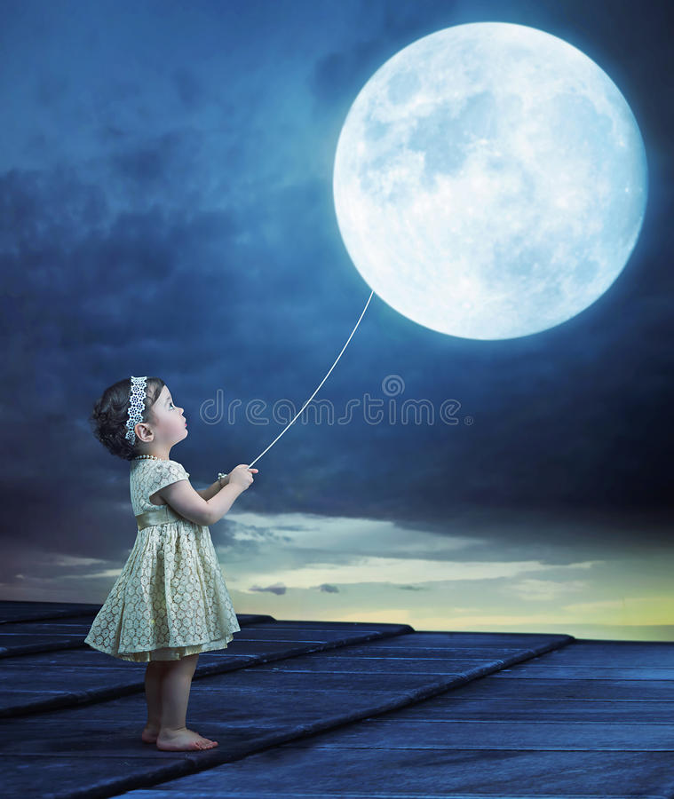 Imagen conceptual de un bebé que sostiene un luna-globo foto de archivo