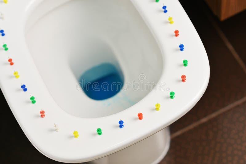 Imagen conceptual de una enfermedad del hemorrhoid con las chinchetas multicoloras en la cubierta de la taza del inodoro imagenes de archivo