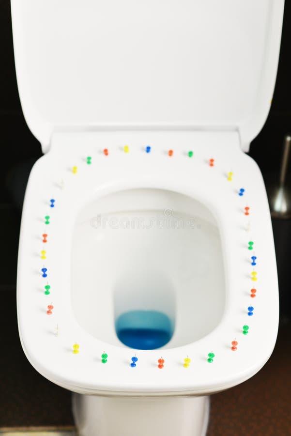 Imagen conceptual de una enfermedad del hemorrhoid con las chinchetas multicoloras en la cubierta de la taza del inodoro imágenes de archivo libres de regalías