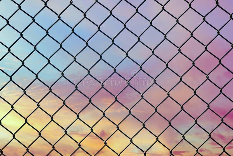 Imagen conceptual del cielo crepuscular con efecto del tono en colores pastel ligero y de la cerca de alambre de acero de la mall imagen de archivo
