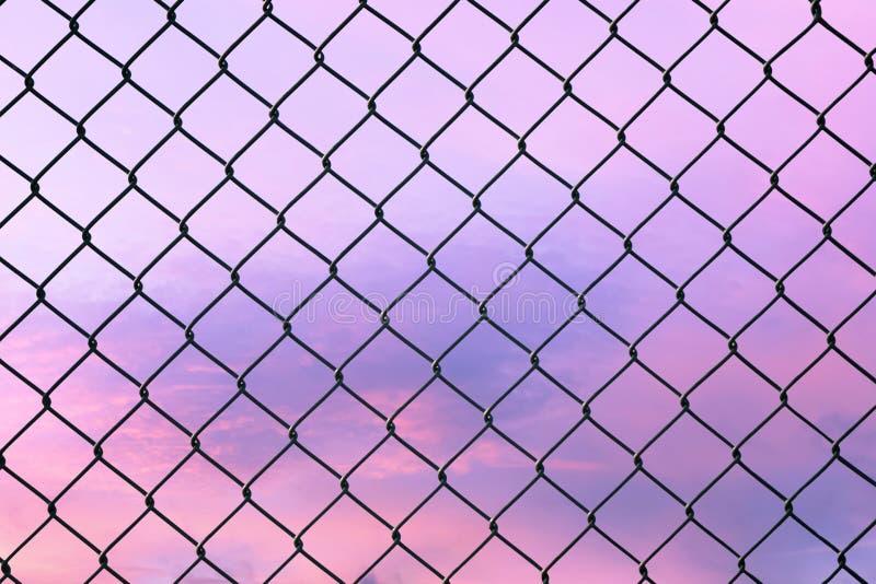 Imagen conceptual del cielo crepuscular con efecto del tono en colores pastel ligero y de la cerca de alambre de acero de la mall imagen de archivo libre de regalías