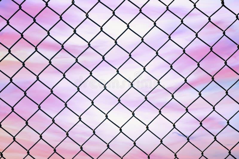 Imagen conceptual del cielo crepuscular con efecto del tono en colores pastel ligero y de la cerca de alambre de acero de la mall imágenes de archivo libres de regalías