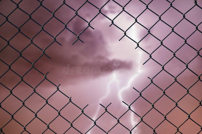 Imagen conceptual del relámpago en el cielo tempestuoso y la cerca de alambre de acero de la malla imagen de archivo