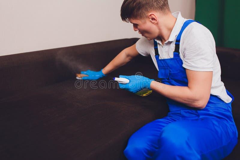 Imagen cosechada Concepto de la limpieza Mano masculina en los guantes protectores azules que limpian el sof? del sof? en el cuar foto de archivo