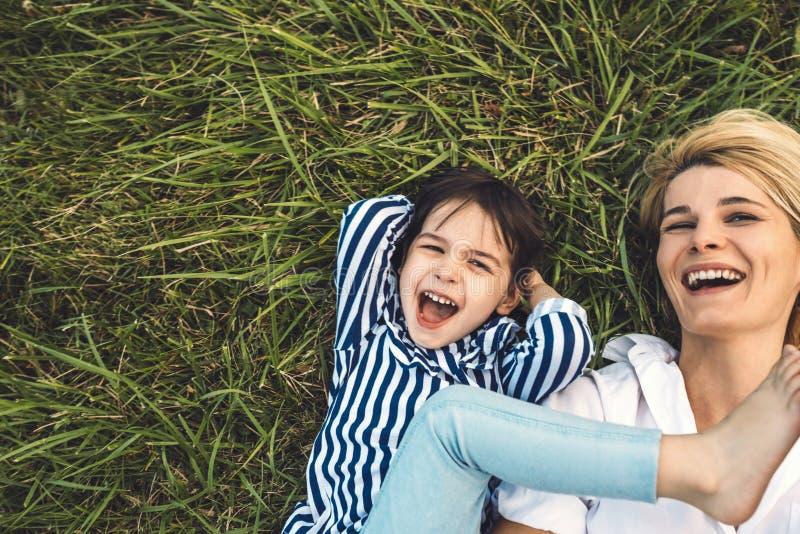 Imagen cosechada de arriba de la mujer hermosa feliz que ríe y que juega con su niña linda en la hierba verde al aire libre lovin imágenes de archivo libres de regalías