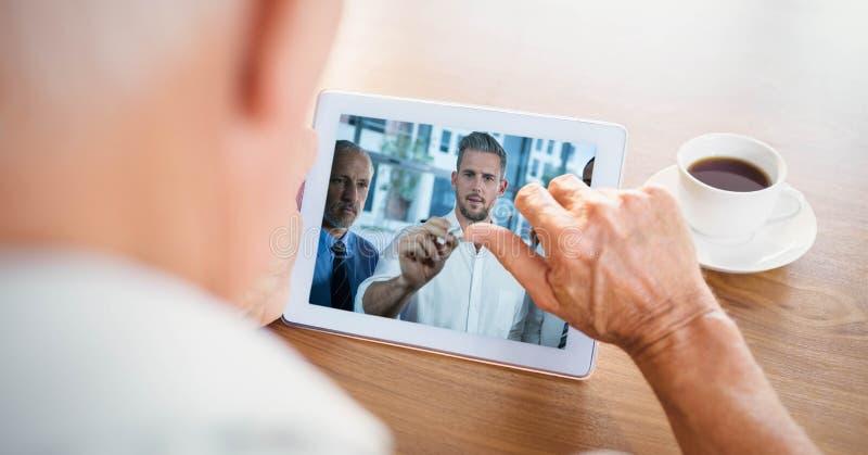 Imagen cosechada de la comunicación video del hombre de negocios con los socios en la tableta imagen de archivo