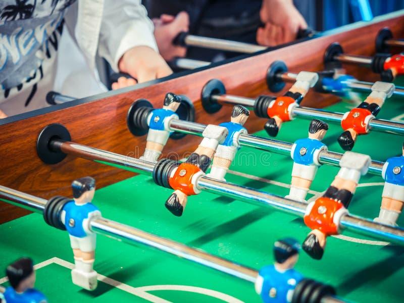 Imagen cosechada de la gente activa que juega el foosball plaers del fútbol de la tabla El juego de los amigos junto presenta el  imagen de archivo libre de regalías