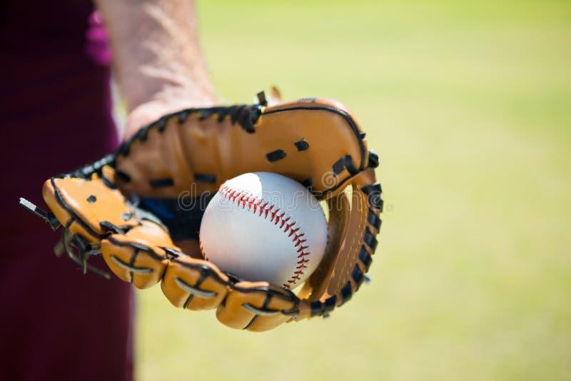 Imagen cosechada de la jarra del béisbol que sostiene la bola en guante fotografía de archivo