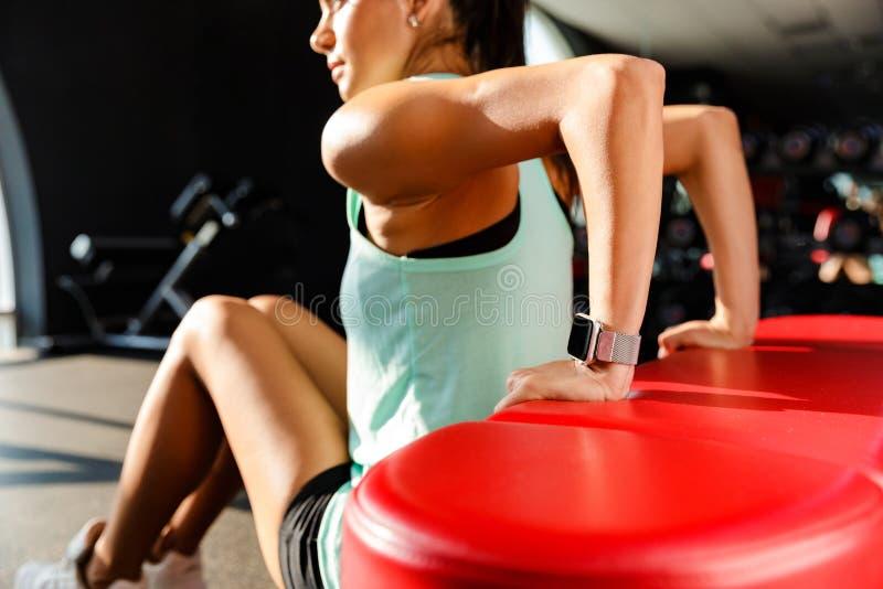 Imagen cosechada de la mujer concentrada de los deportes que hace ejercicio de la aptitud imagenes de archivo
