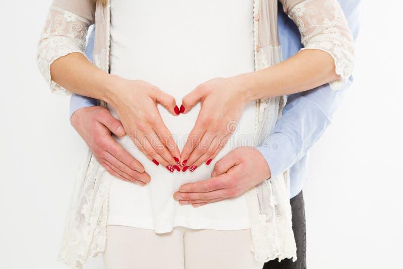 Imagen cosechada de la mujer embarazada hermosa y su del marido hermoso que abrazan la panza Muestra del amor Acontecimiento feli imagen de archivo