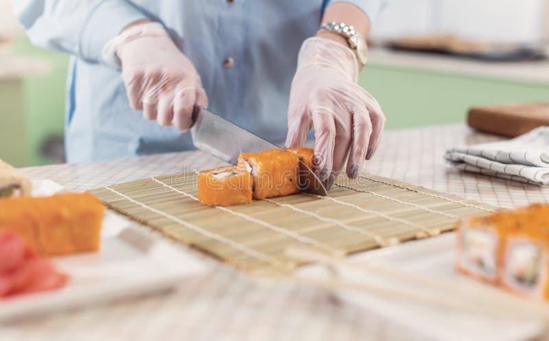 Imagen cosechada de la mujer en los guantes que cortan los rollos de sushi en la estera de bambú y que sirven las placas imagen de archivo libre de regalías