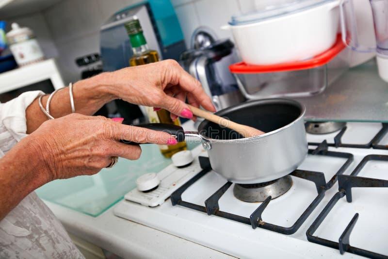 Imagen cosechada de la mujer mayor que cocina en la encimera foto de archivo