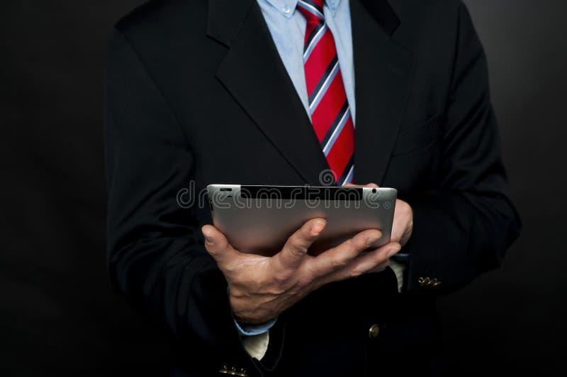 Imagen cosechada de la PC de la tablilla de la ojeada del hombre de negocios fotografía de archivo